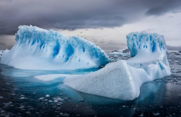 An aerial shot of icebergs in Antarctica under cloudy sky